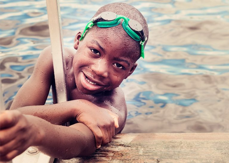 Young boy (Jeremy) smiling while in a lake